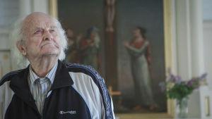 Iäkäs mies katselee ylös kirkossa, taustalla alttarimaalausta