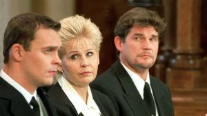 Kotikadun Teemu, Karin ja Hannes istuvat kirkossa. Heillä on mustat vaatteet yllään ja he näyttävät surullisilta.