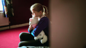 Tyttö istumass yksin lattialla, nojaa seinää vasten ja puristaa pehmolelua.