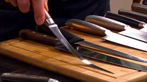 Närbild på en hand som håller i en fileringskniv.