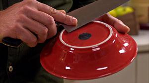 Närbild på en kniv som blir vässt mot en porslinsskål.