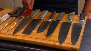 En skärbräda full med olika köksknivar.