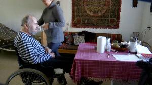 man i rullstol och person bakom