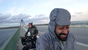 Två personer cyklar på en bro. Det blåser mycket och ser kallt ut. Cyklarna är fullastade med väskor.