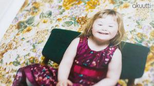 Islantilainen Down-lapsi Brita istuu tuolilla
