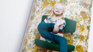 Islantilainn Down-lapsi Katrin istuu tuolilla kuvattavana