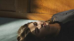 Nainen makaa lattialla.