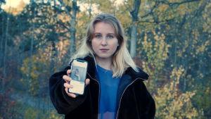En kvinna med långt blont hår. Hon står framför en björkskog. Hon håller upp en telefon där appen Instagram är igång. Vi ser en bild av henne, där hon är lättklädd och väldigt smal, eftersom hon lider av anorexi.
