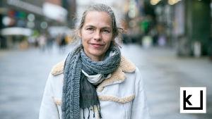 Näyttelijä Katja Kiuru katsoo kameraan kadulla.