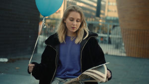 En kvinna med långt blont hår, blå tröja och svart jacka. Sitter utomhus och på en stol och läser tidningen. Hon håller också i en blå heliumballong.