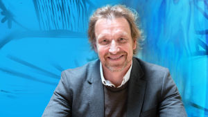 Kuvassa on Marco Mäkinen sinisävyiden taustan edessä
