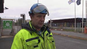 Lars Westerholm står i skyddshjälm och overall framför porten till hamnen i Lappvik.
