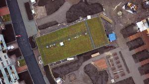 En bild tagen från luften där en förrådsbyggnads gröna tak syns.
