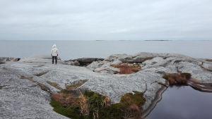Nainen seisoo kivisellä rannalla. Kuva liittyy Radio Variaatio -sarjan ohjelmaan Sulamisvesissä