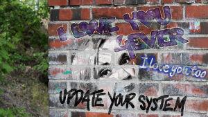 Tekstigraffiteja seinässä, mm. Update your system. Kuva liittyy Radio Variaatio -sarjan ohjelmaan Kohta rakkaus loppuu
