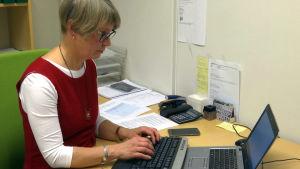 En kvinna skriver på en dator.