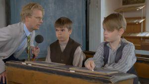 Oskar Pöysti pratar in i örat på en elev för att visa vad Topelius menade med korvstoppning.