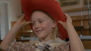En liten flicka provar en röd hatt.