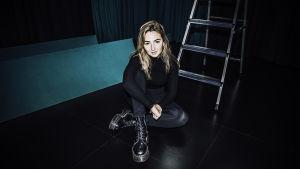 Laulaja Erika Sirola istuu kuvassa lattialla jalat ristissä.