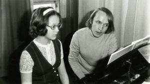 Tuleva musiikkitieteen professori Eero Tarasti opettaa pianonsoittoa tulevalle mezzosopraano Monica Groopille Meri Louhoksen pedagogiikkatunnilla 1960-luvun lopulla.