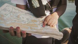 Oppilas tutkii merikarttaa ja navigoi sen avulla.