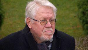 äldre man med glasögon