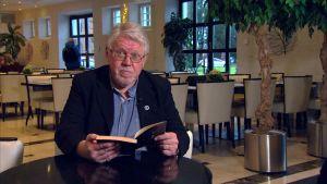 äldre man läser ur bok
