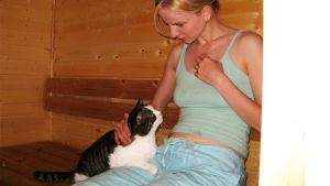 Nainen ja kissa saunanlauteilla.