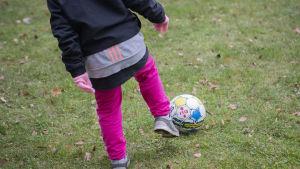 Lapsi pelaa jalkapalloa.