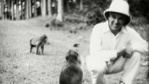 Charlie Chaplin kyykyssä hiekkatiellä, jossa kaksi apinaa. Katsoo kameraan.