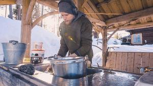 En mat lagar mat i ett ute kök med hörlurar på huvudet. Det är vinter.