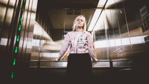 Vaaleahiuksinen nainen katsoo suoraan kameraan hississä.