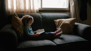 Kuvassa tyttö lukee sohvalla.