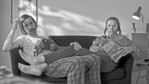 Mies ja nainen istuvat sohvalla.