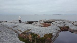 Henkilö seisoo kaukana kalliolla pukeutuneena valkoiseen takkiin katsoen kauas horisonttiin.