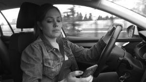 Nainen autossa matkapuhelin kädessään.