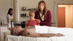 Nainen ja tyttö sairaalasängyn vieressä, jossa makaa mies.