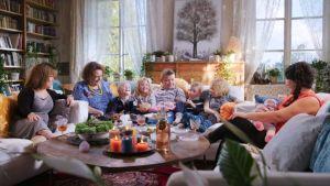 Lindan perhe ja läheiset sohvalla Mapen vieraina. Kaikki nauravat iloisesti.