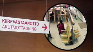 Skylt där det står akutmottagning och en spegel där en kvinna som sitter och väntar syns.