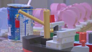En handgjord färggrann leksaksbåt, målburk i bakgrunden.