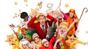 Mies pitää käsillään päätään pienten, värikkääsi pukeutuneiden lasten keskellä.