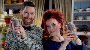 Mies ja nainen pitää shakerin käsissään ja hymyilee kameralle.