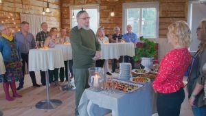 Eijan Timo-serkku pitää puhetta Eijalle. Eija on punaisessa paidassaan selkä vasten kameraa ja Timon ja hänen välillään on pöytä täynnä hedelmiä ja muita herkkuja. Muut serkut seisovat taustalla.