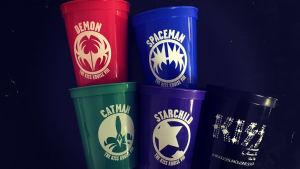 Fem Kiss-muggar av plast. Röd Demon, grön Catman, Lila Starchild och blå Spaceman samt ebn svart kiss förfestmugg. Kiss Kruise VIII 2018.