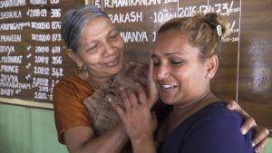 äldre kvinna i indiska kläder tröstar yngre kvinna