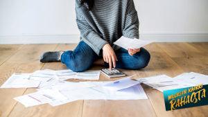 Nainen tutkii lattialla lojuvia laskuja.