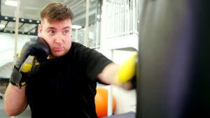 Mies nyrkkeilee säkkiä.