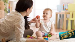 Kuvassa nainen ja lapsi leikkimässä lattialla.