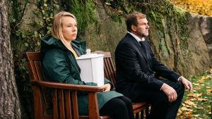 Radioteatteri esittää: Kellonkissaniitty. Kuvassa nainen ja mies istuvat ulkona puisella penkillä. Naisella sylissään tuhkauurna.