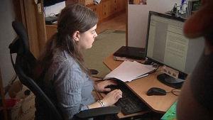 Kirjailija Minttu Vettenterä istuu tietokoneella.